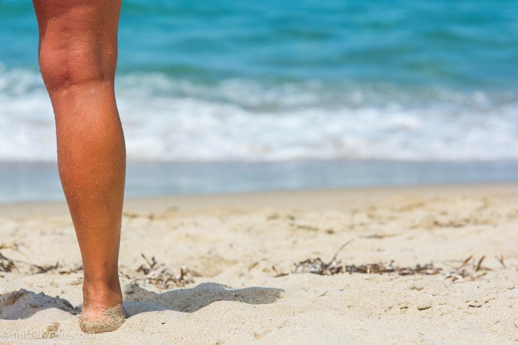 Schöne Beine am Strand von Sardinien.